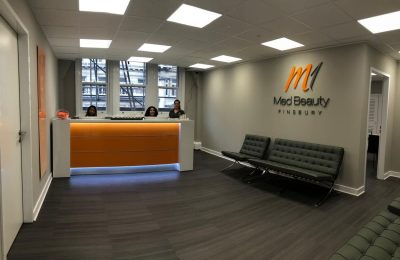 Treatment room from our M1 Med Beauty clinic with orange counter and modern equipment